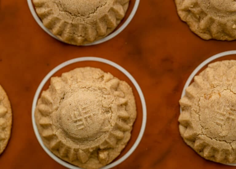 overhead closeup image: tops of buttery mamool cookies on baking sheet