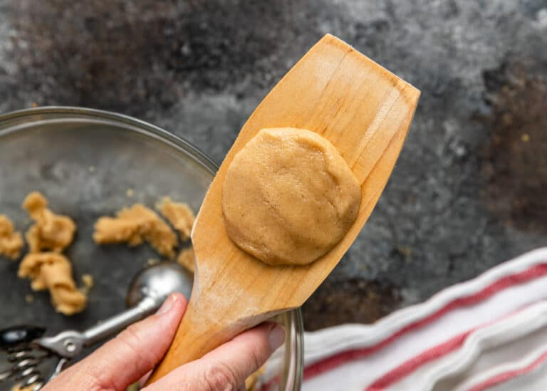 circle of unbaked semolina cookie dough on wooden spatula