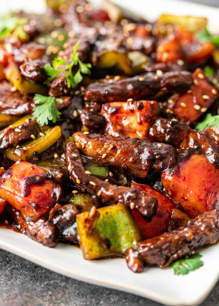 close up: steak stir fry with vegetables and sesame seeds in dark sauce
