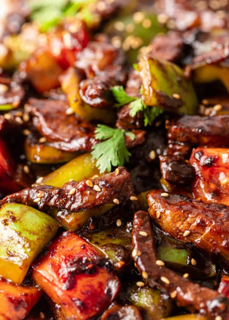 close up of stir fried pepper steak with onion and tomatoes