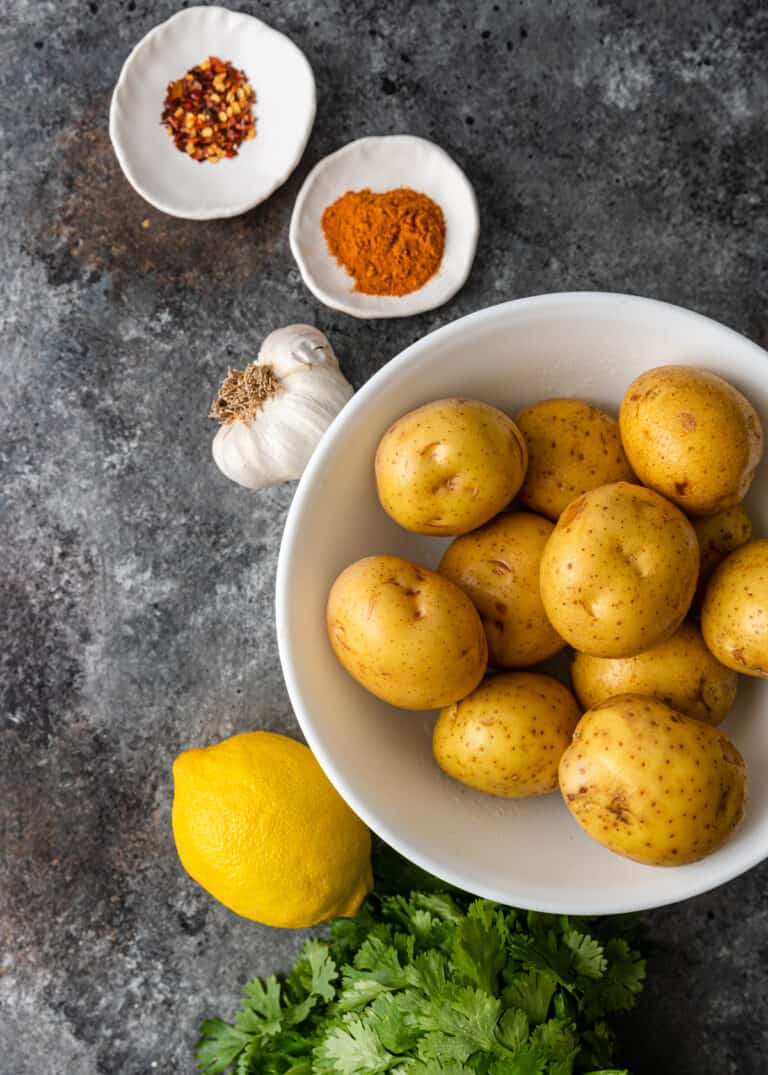 overhead white bowl of yukon gold potatoes with dishes of lebanese spices