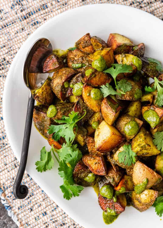 overhead closeup: white dish of roasted lebanese potatoes and serving spoon