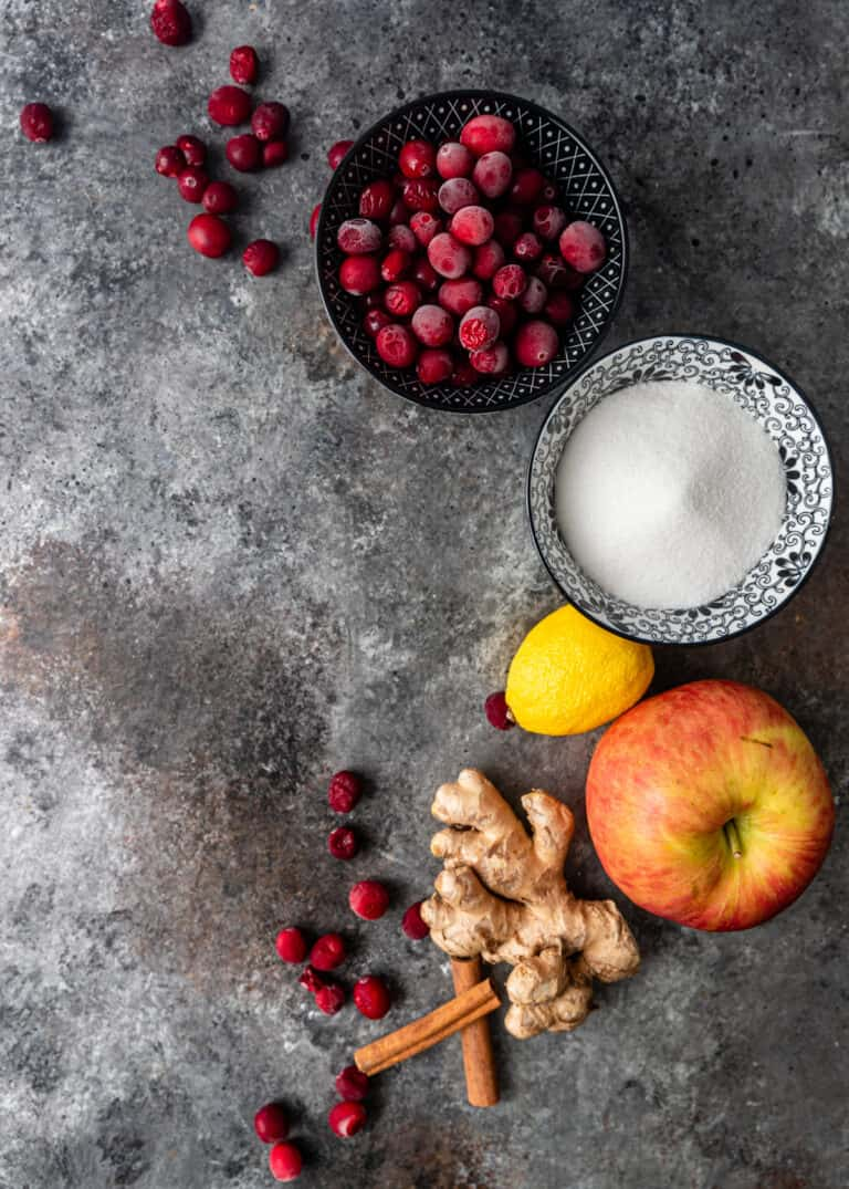 overhead: bowls of fresh cranberries and white sugar with fresh red apple and ginger root