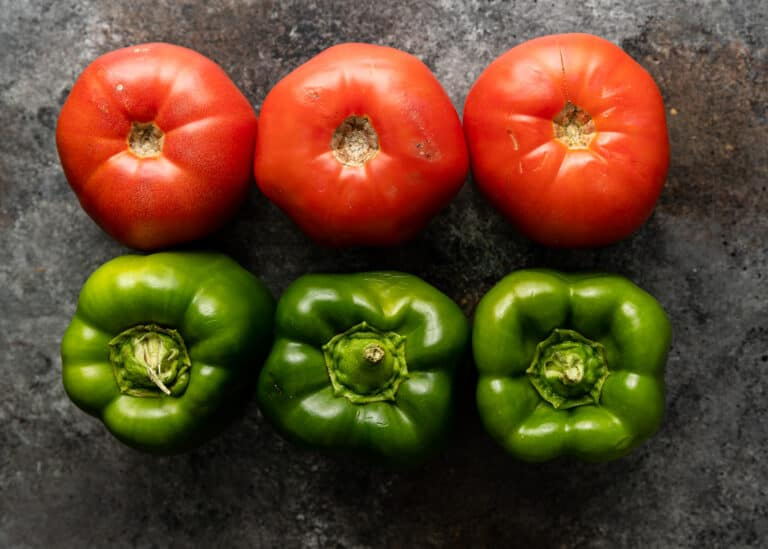 overhead: 3 fresh red tomatoes and 3 bell peppers on gray background