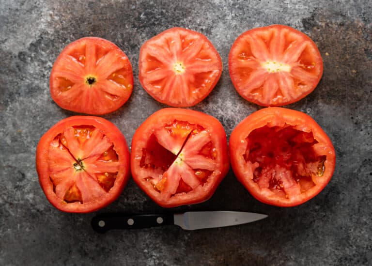 overhead: 3 large red tomatoes with insides removed for stuffing