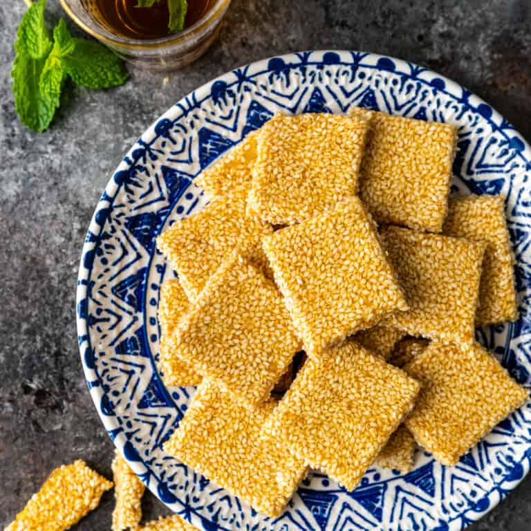 overhead: square of sesame snaps on blue and white plate