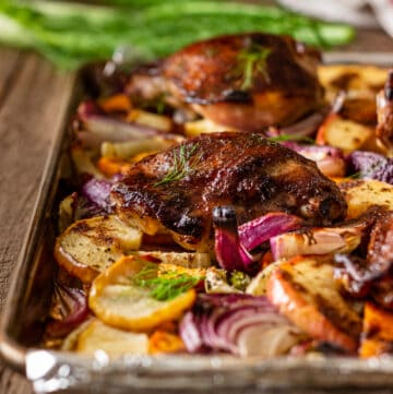 crispy roasted chicken thighs on baking sheet with slices of fennel, sweet potatoes and red apple